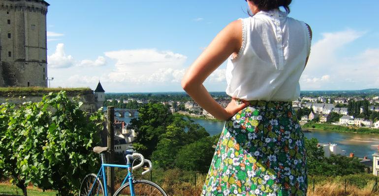 Femme tenue et vélo vintage contemplant le château de Saumur et la Loire