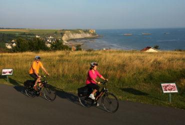 2 cyclistes avec au loin la plage d'Arromanches à vélo Normandie