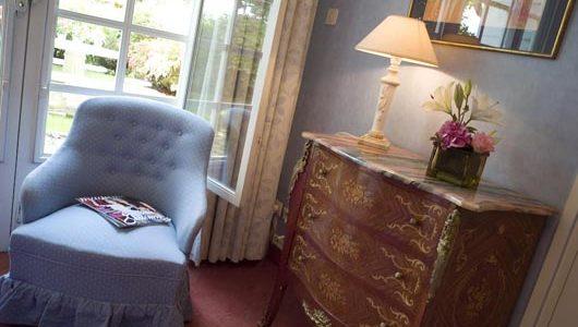 Fauteuil et commode dans une chambre Hôtel le Chateau De Beaulieu à Joué-lès-Tours Abicyclette Voyages à vélo