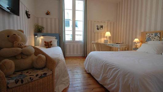 Chambre grand lit et lit enfant fauteuil avec oursons en peluche Hôtel Le Londres Abicyclette Voyages à vélo