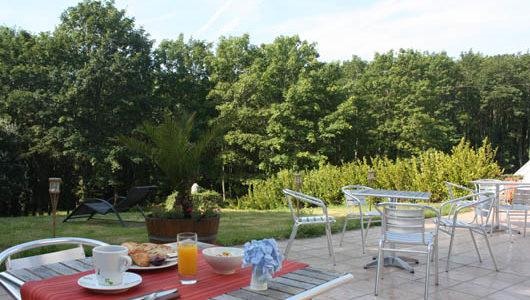 Petit-déjeuner en terrase donnant sur jardin arboré Hôtel Latitude Ouest à Locronan Abicyclette Voyages à vélo