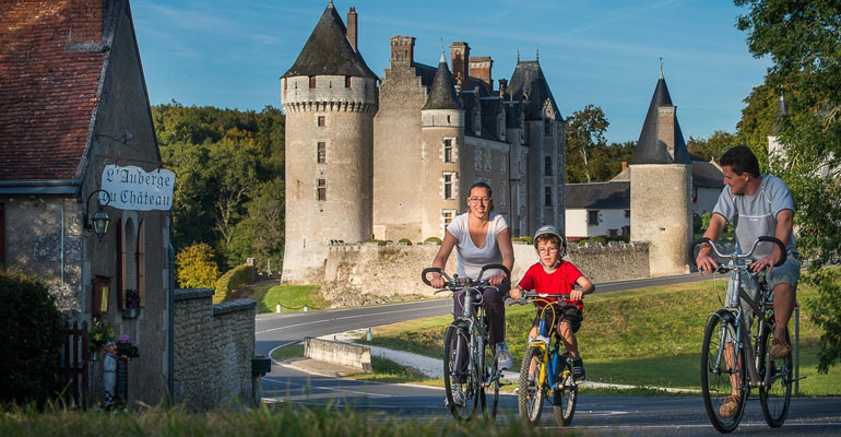 Famille à vélo devant une auberge et un château Loire à vélo
