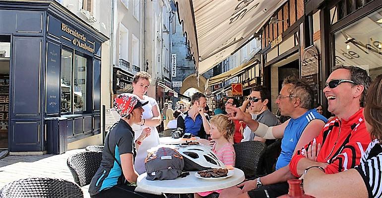 Groupe de cycliste à une terrasse dans une rue piétonne d'Amboise Abicyclette Voyages à vélo