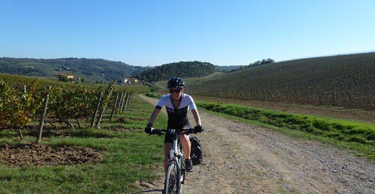Cycliste sur chemin de terre au milieu des vignes L'italie à vélo Abicyclette Voyages