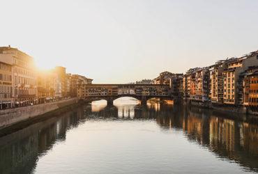 Florence à vélo vue du fleuve avec pont et maisons