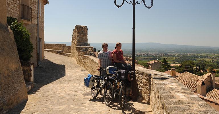 Couple de cyclistes devant panorama de la campagne provençale, halte vacances à vélo en Provence