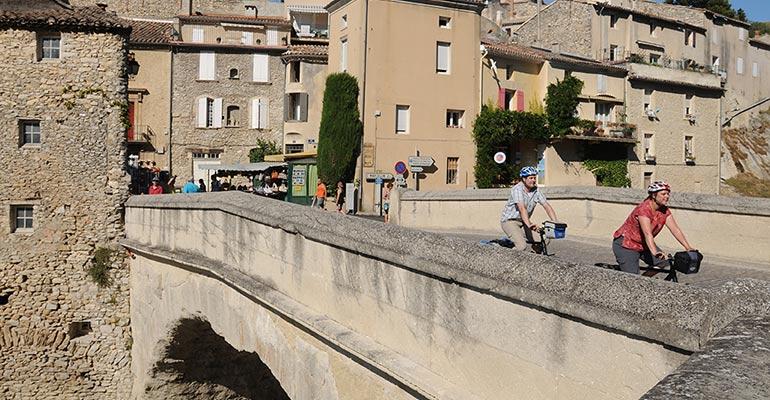 2 cyclistes traversant le pont de Vaison la Romaine, étape vacances à vélo en Provence