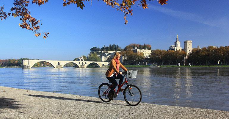 Cycliste le long du Rhône avec en arrière-plan le Pont et la ville d'Avignon, destination vacances à vélo en Provence