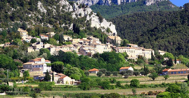 Villange au pied d'une falaise et surplombant des vignes, vacances à vélo en Provence