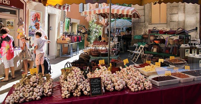 Etals d'ail, d'huile d'olive et d'artisanat sur un marché vacances à vélo en Provence