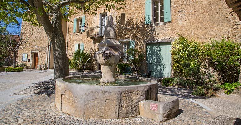 Vieille fontaine sur une place village vacances à vélo en Provence