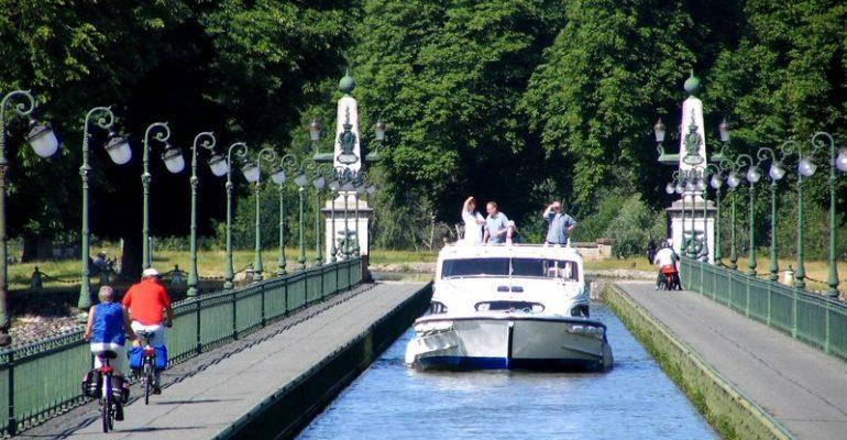 cyclotouristes croisent un bateau sur le pont-canal de briare séjour à vélo