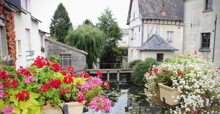 Rivière avec fleurs et et vieilles batisses dans village sur les bords de la loire a velo
