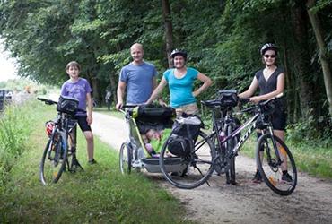 Photo d'une famille avec ses vélos pause en forêt pendant vacances à vélo