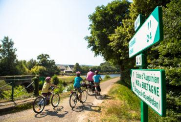Famille de cyclistes pendant leurs vacances à vélo en Bretagne devant panneaux de direction itinéraire à vélo