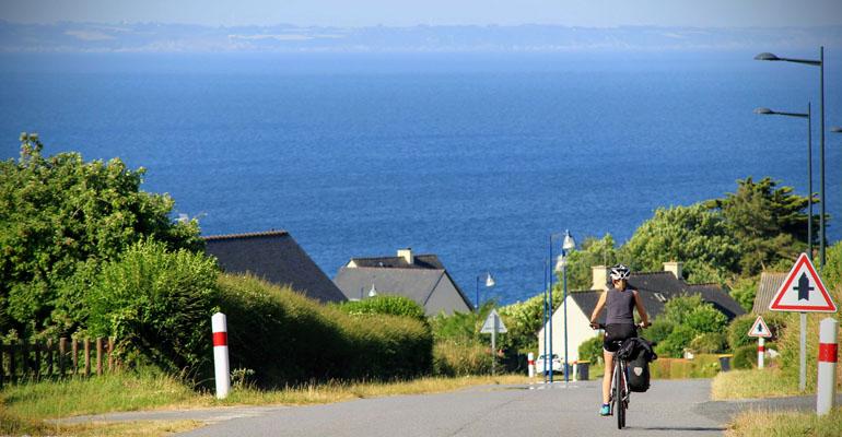 Cycliste dans une descente vers la mer à Crozon étape séjour à vélo
