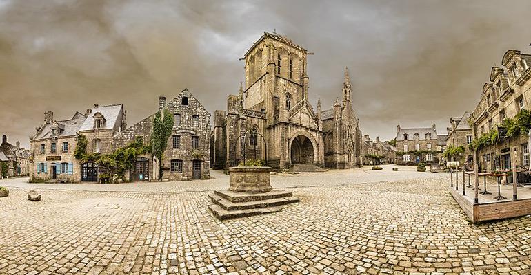 Locronan place pavée avec vieille église et bâtiments anciens étape séjour à vélo