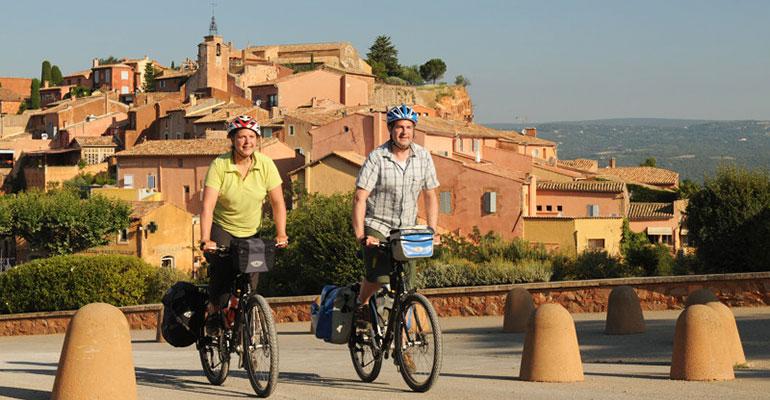 Couple à vélo en danseuse à la sortie d'un village Le petit tour du Luberon