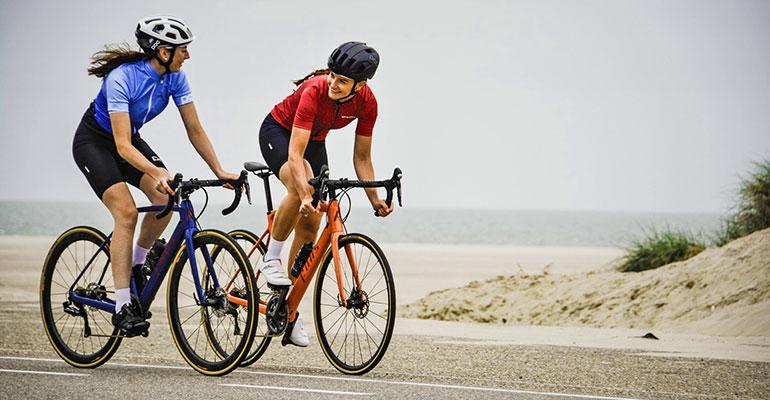 2 femmes cyclistes se regardent roulent devant la plage