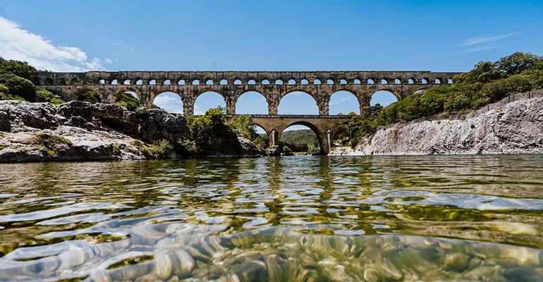 le pont du gard depuis la riviere sous le soleil