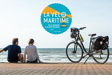 couple au bord de la mer sur promenade en brique, un vélo avec casque accroché logo vélomaritime