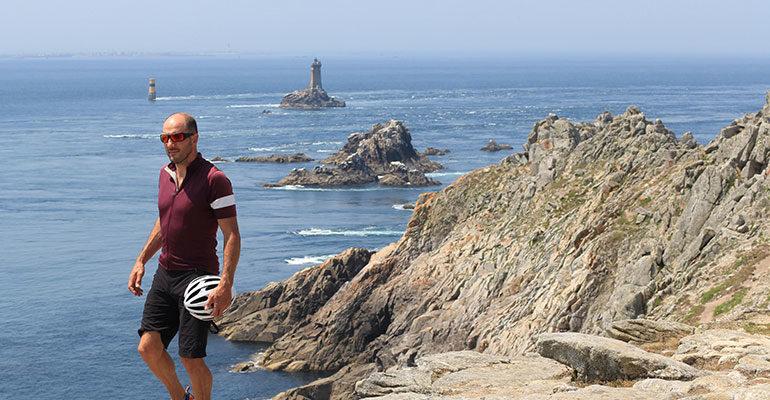Un cycliste marche sur le sentier côtier à la pointe du Raz