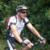 voyageur à vélo en t-shirt blanc et casque gris