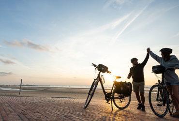 2 cyclistes sur une vaste plage, fiers d'être arrivés à destination