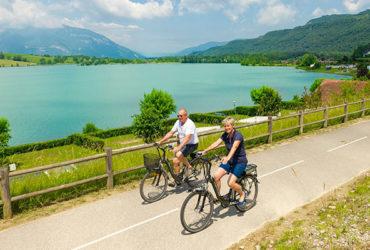 Couple à vélo le long du Rhône sur la ViaRhôna, lac et montagne